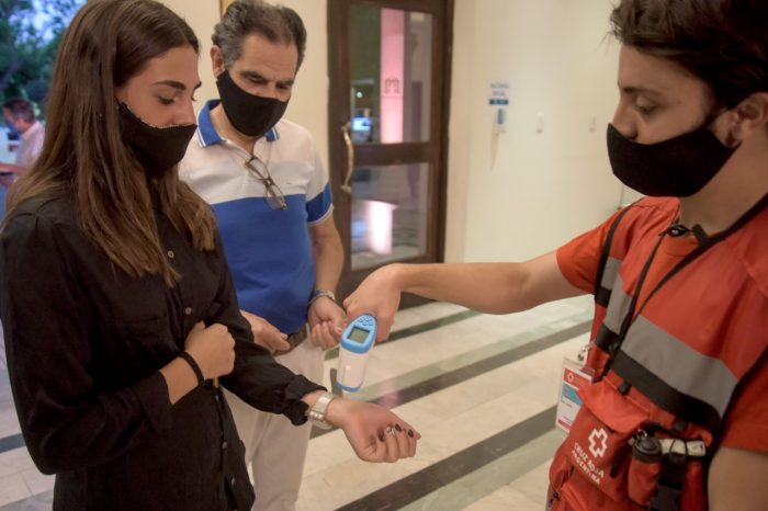 Un miembro de la Cruz Roja toma la temperatura a una mujer.