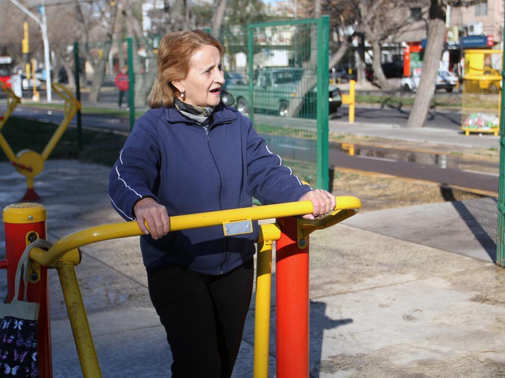 mujer mayor calentando en equipos de gimnasio al aire libre